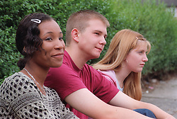 Multiracial group of teenagers sitting on a park bench,