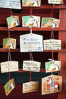 """Ema are small wooden plaques on which Shinto worshippers write their prayers or wishes. The votive tablets or ema are then left hanging up at the shrine where the spirits or gods receive them. They usually bear various pictures of animals or other Shinto imagery and many have the word gan'i meaning """"wish"""" written along the side."""