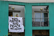 """A supporter of Black Lives Matter movement's cause opened a banner """"Black Lives Matter"""" at her balcony opposite Tottenham Police Station in North London, on Saturday, Aug 8, 2020 - as a number of British-African drummers and speakers' address racial injustice to the crowd of anti-police brutality protestors carrying banners, placards, and flags.<br /> Black Lives Matter enters the 11th weekend of continuous demonstrations against racial injustice in Britain. <br /> Anger against systemic levels of institutional racism has raged and continued throughout the United States, Britain and worldwide; sparked by the death of George Floyd who died on May 25 after he was restrained by Minneapolis police in the United States. (VXP Photo/ Vudi Xhymshiti)"""
