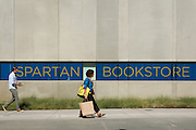 Students walk past signage outside the new Spartan Bookstore at San Jose State University in San Jose, California, on August 22, 2014. (Stan Olszewski/SOSKIphoto)