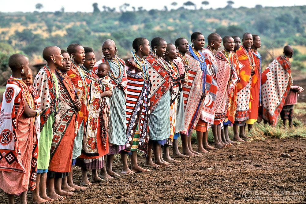 Maasai women perform a traditonal welcome including singing and dancing for tourists visiting their village (manyatta) in the Masai Mara in Kenya.