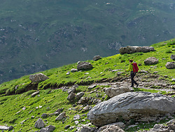 Woman hiking in the High Pyrenees descending from Hourquette d'Alans towards Pont d'Estaube, Gavarnie, France
