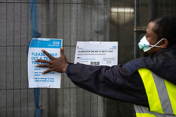 © Licensed to London News Pictures . 16/09/2020. Bolton , UK . A man in a high visibility jacket attempts to cover over an NHS Test and Trace advice sign fixed to railings outside a testing site in Farnwoth . The number of recorded cases of Coronavirus has gone over 200 in a single day , in Bolton . Photo credit : Joel Goodman/LNP