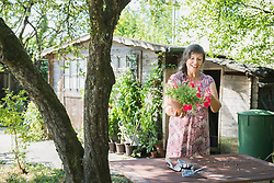 Senior woman repotting flowers, Altoetting, Bavaria, Germany