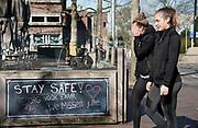Nederland, Nijmegen, 23-03-2020 In de binnenstad is op een windscherm van een gesloten terras de wens stay safe, blijf veilig, zorg voor elkaar, geschreven om voorbijgangers een hart onder de riem te steken .Foto: Flip Franssen.