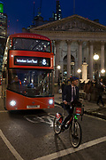 A cyclist on a Santander rental bike pauses at traffic lights in front of a number 8 Routemaster bus in Threadneedle Street and opposite the columns of Cornhill in the heart of the Square Mile, the capital's historical and financial centre, on 1st November 2017, in the City of London, England.