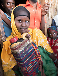 27 January 2019, Burka Dare IDP site, near Micha, Seweyna woreda, Bale Zone, Oromia, Ethiopia: 18-year-old Sahara Abdullahi makes covers for jerry cans, to keep water from heating in the sun. The covers offer her a source of income, as she sells them at a price of 50 Birr. The Lutheran World Federation supports internally displaced people in several regions of Ethiopia, through emergency response on water, sanitation and hygiene (WASH) as well as long-term development and empowerment projects, to help build resilience and adapt communities' lifestyles to a changing climate.