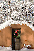 A traditional door on an adobe style home decorated with a Christmas wreath in the Arroyo Tierra Blanca neighborhood after a winter snowfall in Santa Fe, New Mexico.
