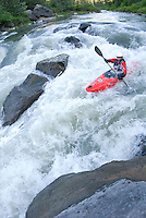 A young woman kayaks the whitewater on the Teton River in eastern Idaho.