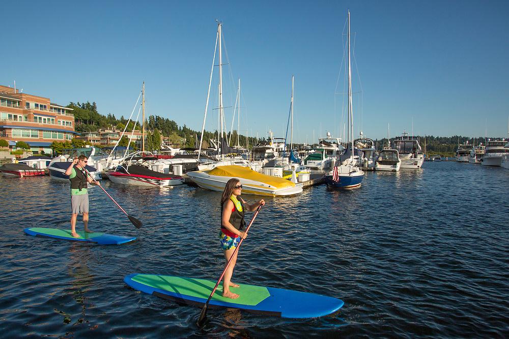 United States, Washington, Kirkland, poople on stand up paddleboards on Lake Washington near Carillon Point Marina.  MR