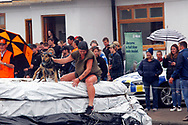 Hunterville, New Zealand - October 27, 2018 - Shepherds have to jump with their dogs into a tank full of water and muck that is traditionallly used for dipping cattle in the annual Shemozzle obstacle race in which the canines and shepherds tackkle mudslides, ride in wheel barrows and carry bulls testicles. Here a shepherd is seen emerging from the tank with her dog. The annual Shemozzle race draws thousands every year to this town of less than 500 people. Picture: Giordano Stolley