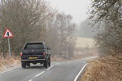 © Licensed to London News Pictures. 13/02/2021. Builth Wells, Powys, Wales, UK. Motorists drive along the B4520 (Brecon road) in strong south east winds and snow with temperatures around minus 4.5 deg C and 'feels like' temperature around minus 10-15 deg C at 400 metres (1,300 feet) above sea-level on the Mynydd Epynt range near Builth Wells in Powys, Wales, UK. Photo credit: Graham M. Lawrence/LNP