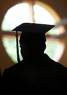A Jeffersonville-Youngsville graduate is silhouetted in the gymnasium window during commencement exercises at the school in Jeffersonville on June 24. (Tom Bushey photo. June 24, 2000).