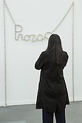 "New York, NY - 6 May 2016. Frieze New York art fair. A woman looks at a sculpture on nickel-plated steel chain titled ""Prozac,""by Monica Bonvicini, in Berlin's König Galerie."