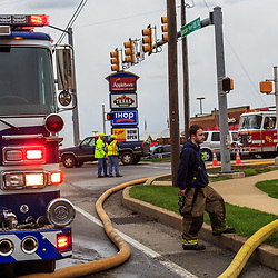 Lancaster, PA, USA- April 14, 2015: A firefigter stands by a fire hydrant at a motel fire.