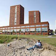 """Nederland Rotterdam 30-05-2009 20090530 Foto: David Rozing ..Nieuwbouw woningen in probleemwijk Katendrecht, man leest boek aan het strandje terwijl een kind in het zand speelt, met op de achtergrond de nieuwbouw woningen en euromast. Stedelijke vernieuwing, relaxen, relaxed, ontspanning, vrije tijd, van het zonnetje genieten, zomers, lekker weer, zomerse dag, zomers, zonnig, zonnige, zon, genieten, ontspanning, rust, huisje boompje beestje, ruime moderne wijk, vrij uitzicht, strand New houses / appartments in (former) deprived area / projects """"Katendrecht """" This area is on a list with projects which need help of the government because of degradation in the area etc   .city, beach, project, suburb, suburbian, problem. Neighboorhood, neighboorhoods, district, city, problems,  daily life Holland, The Netherlands, dutch, Pays Bas, Europe ..Foto: David Rozing"""