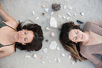 Two Women sharing a crystal aura on a perfect wild sand surface.