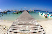 Wooden pier with Pongas tied up.  This is on the lee side of the tiny island of Isla Mujeres, Quintana Roo, MX.
