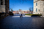 A child on a bycicle at the beginning of Charles Bridge on the left, Prague Castle in the back. On March 1st, 2021 the state of emergency in the Czech Republic was reinstalled because of fast increasing numbers in infections. The lockdown was reinstated and the restriction of the free movement of people has taken effect. Currently, the country remains at the highest stage of the anti-epidemiological system and the newly imposed restriction will last at least three weeks to curb the epidemic.