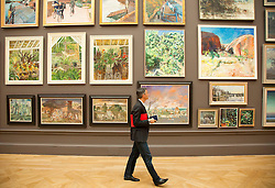 © licensed to London News Pictures. LONDON, UK  02/06/11. A visitor  to the Royal Academy of the Arts Summer Exhibition walks past a wall of paintings. The Royal Academy of the Arts Summer Exhibition is the largest open contemporary art exhibition in the world, with pieces contributed by established, unknown and emerging artists. Please see special instructions for usage rates. Photo credit should read Matt Cetti-Roberts/LNP