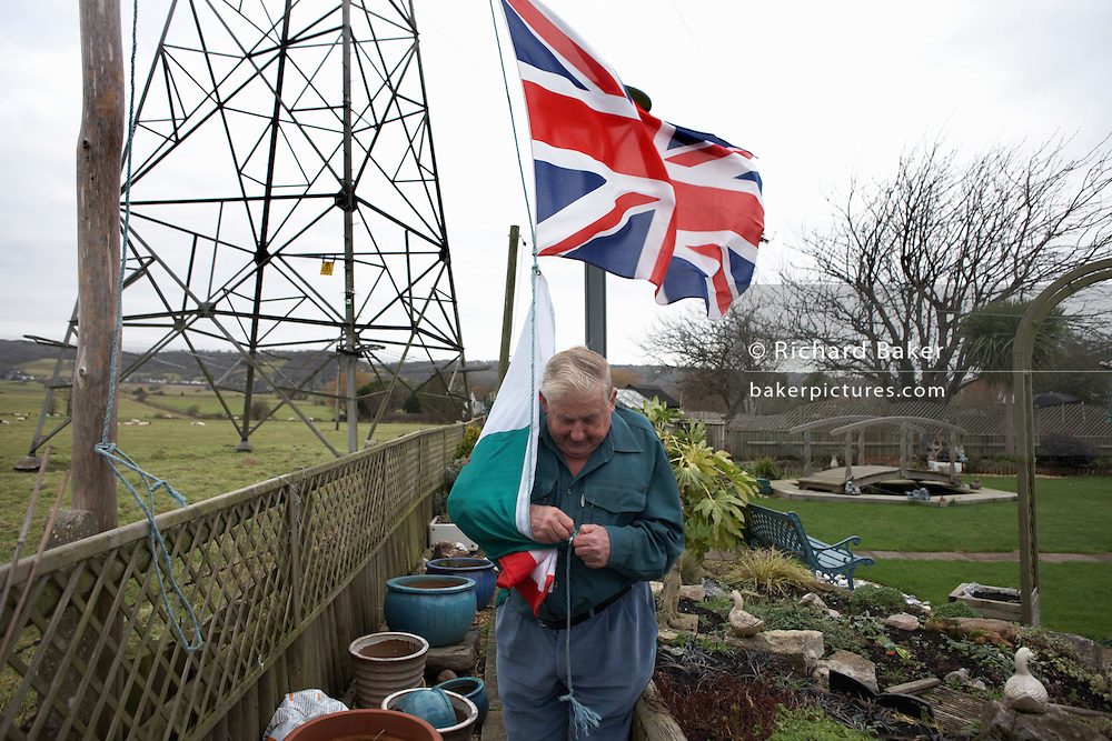 Patriotic pensioner Ivor Dowling attaches the Welsh flag beneath the Union Jack to fly in his back Somerset garden.