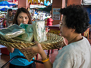 """10 AUGUST 2014 - BANGKOK, THAILAND:     Women pray with a basket of food staples they donated to the Poh Teck Tung Foundation on the first day of Ghost Month in Bangkok. The seventh month of the Chinese Lunar calendar is called """"Ghost Month"""" during which ghosts and spirits, including those of the deceased ancestors, come out from the lower realm. It is common for Chinese people to make merit during the month by burning """"hell money"""" and presenting food to the ghosts.  PHOTO BY JACK KURTZ"""