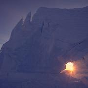 Sunlight shining through a hole in a tabular iceberg at Emperor Penguin rookery in Antarctica.
