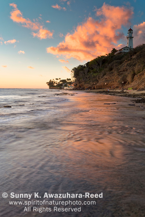 Magenta clouds over Diamond Head Lighthouse and Diamond Head Beach Park at sunset. Honolulu, Oahu Island, Hawaii.