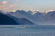 A boat travels up Pitt Lake with mountain peaks from the Garabaldi Ranges in the background.  Photographed from the Katzie Loop trail in Pitt Meadows, British Columbia, Canada.