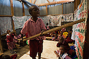 With the aid of a long stick and a homemade cloth poster of numbers 5 year old George stands on the table counting to 1 to100 at the top of his voice along with the rest of his class.