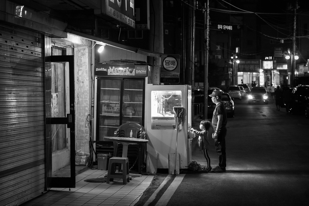 A Father watches as his daughter attempts to win a prize. Paengsong, South Korea