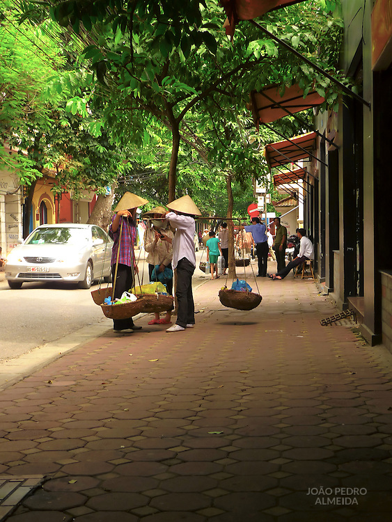 Three women vendors talking at the streets of Hanoi