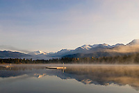 Early morning mist rises gold, autumn in Whistler, BC Canada