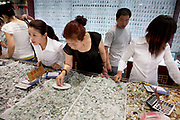 Customers shopping for jade in a jade store in an area just south of Tiananmen in Beijing, China. There is a long history of carved jade in China and it can be bought in any shape or size.