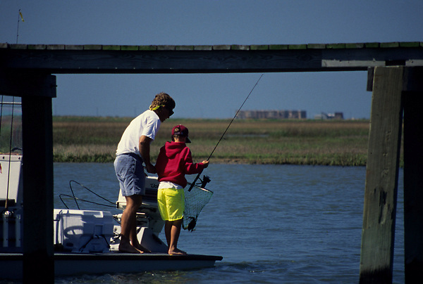 Stock photo of a man netting his son's catch from a small boat by the pier