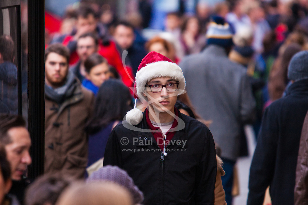 """London, December 23rd 2014. Dubbed by retailers as the """"Golden Hour"""" thousands of shoppers use their lunch hour to do some last minute Christmas shopping in London's West End. PICTURED: A shopper in a Santa hat makes his way along Regent Street."""