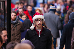 "London, December 23rd 2014. Dubbed by retailers as the ""Golden Hour"" thousands of shoppers use their lunch hour to do some last minute Christmas shopping in London's West End. PICTURED: A shopper in a Santa hat makes his way along Regent Street."
