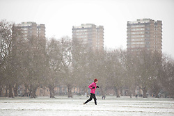 London,UK. 8th Feb 2021. A member of the public jogs through Victoria Park in East London during a snow shower. Snow is expected for large parts of the UK and a yellow weather warning is in place in parts of England as Storm Darcy hits the UK.