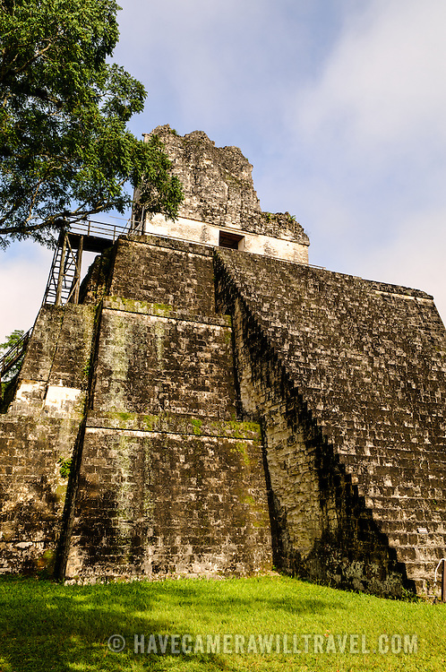 The Temple of the Masks (or Temple 2) on one side of the Main Plaza in the Tikal Maya ruins in northern Guatemala, now enclosed in the Tikal National Park. At left, you can see some of the wooden stairs that have been added in recent years to allow tourists to walk to the flat platform near the top of the pyramid.