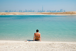Skyline of Dubai from The Island Lebanon beach resort on a man made island, part of The World off Dubai coast in  United Arab Emirates