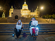 17 DECEMBER 2019 - DES MOINES, IOWA: People sit in front of the Iowa State Capitol and call for the impeachment of President Donald Trump. About 300 people came to the Iowa State Capitol in Des Moines in near freezing weather Tuesday evening to call for Trump's impeachment. The rally, and others like it around the US, come on the eve of an impeachment vote in the US House of Representatives.    PHOTO BY JACK KURTZ