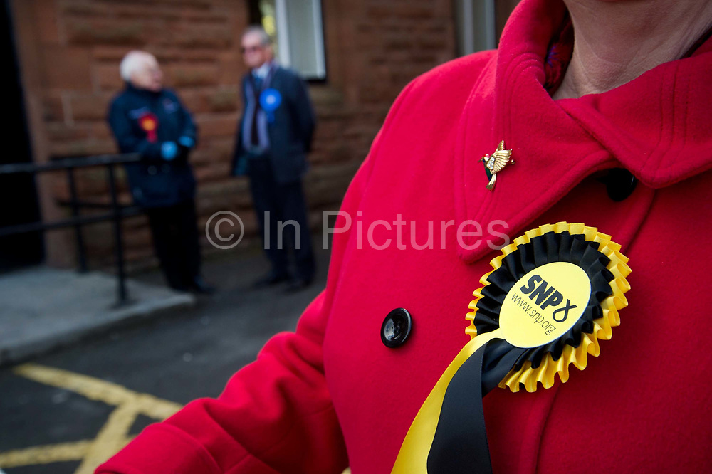 General election 2015. West Kilbride, Scotland. Observers at polling place from SNP, Labour and Conservative parties, with only SNP in focus