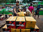 22 NOVEMBER 2017 - YANGON, MYANMAR: Workers put cases of Burmese liquor onto pallets before it's loaded into the hold of a cargo ship taking the liquor up the Irrawaddy River. Myanmar's road system lags behind its neighbors in Southeast Asia and a lot of cargo is still moved by ships and barges.    PHOTO BY JACK KURTZ