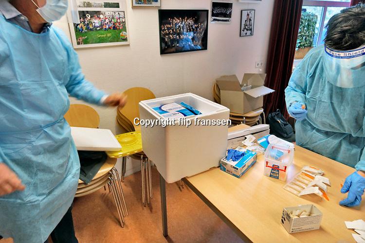 Nederland, Berg en Dal, 28-10-2020 Ouderen laten zich via de huisarts inenten met een griepvaccin. Het is de jaarlijkse inentingscampagne voor 60-plussers. Vanwege de coronaepidemie worden de mensen in het plaatselijke dorpshuis ingeent . Ook zijn mondkapjes en anderhalvemeter afstand bewaren verplicht en dragen de zorgmedewerkers beschermende kleding om besmetting te voorkomen .Foto: ANP/ Hollandse Hoogte/ Flip Franssen