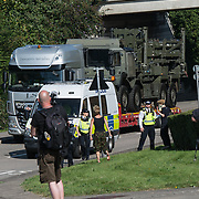 A large truck carries a military tractor to the arms fair in Excel London, UK.