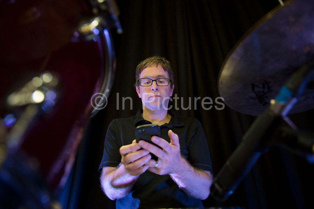 Drummer David Narcizo checks his phone messages during soundcheck. Throwing Muses at the Islington Assembly Hall, London, UK. Throwing Muses are an alternative rock band founded in 1980. The group was originally fronted by two lead singers, Kristin Hersh, and Tanya Donelly. Known for performing music with shifting tempos, creative chord progressions, unorthodox song structures, and surreal lyrics, the group was set apart from other contemporary acts by Hersh's stark, writing style, David Narcizo's unusual drumming techniques almost totally without cymbals and Bernard Georges' driving baselines.