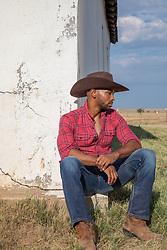cowboy sitting by a rustic barn on a ranch