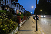Cars drive past Edwardian-era homes in a residential south London street in early evening, 7th August 2020, in Lambeth, London, England.