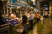 People shopping at fishmonger stalls inside historic covered market building, Jerez de la Frontera, Spain