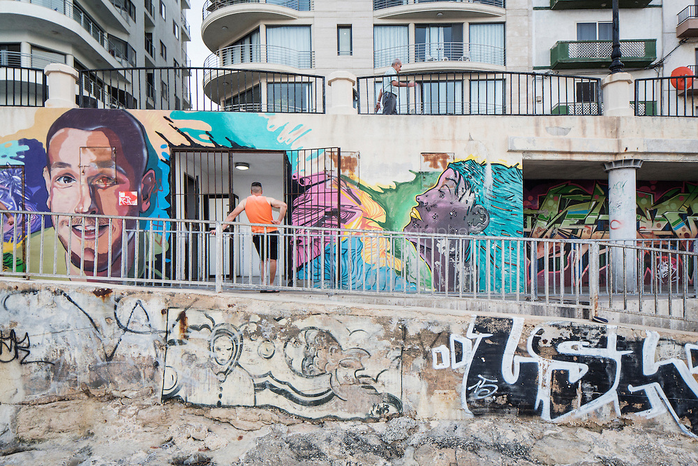 """SLIEMA, MALTA - 28 AUGUST 2016: People relax at sunset by a mural along the coast in Sliema, Malta, on August 28th 2016.<br /> <br /> While many cities across the world denounce the defacing of a public property, on the Mediterranean island of Malta it is encouraged.<br /> <br /> According to Sandra Borg of Arts Council Malta, street art projects """"engage with numerous communities and contribute directly to urban regeneration"""". Funding from Arts Council Malta, allows schools to offer additional creative arts subjects and many choose street art; with 'NO WAR' creator, James Grimaud, teaching students sketching, stencil making and aerosol use."""